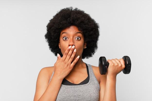 Zwarte afro fitness vrouw met een dumbbell