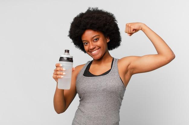 Zwarte afro fitness vrouw met een handdoek en waterkan