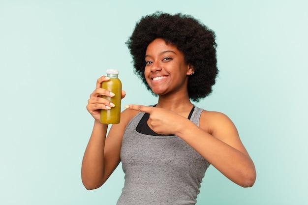 Zwarte afro fitness vrouw met een smoothie