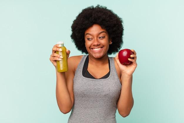 Zwarte afro fitness vrouw met een smoothy