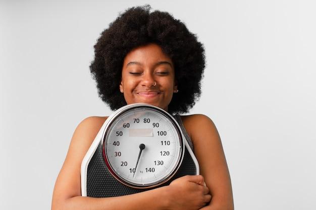 Zwarte afro fitness vrouw met een weegschaal of weegschaal