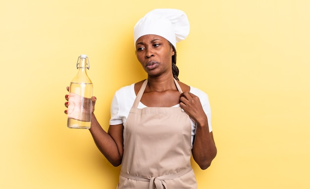 Zwarte afro-kokvrouw voelt zich gestrest, angstig, moe en gefrustreerd, trekt aan de nek van het shirt, ziet er gefrustreerd uit over het probleem met het vasthouden van een waterfles
