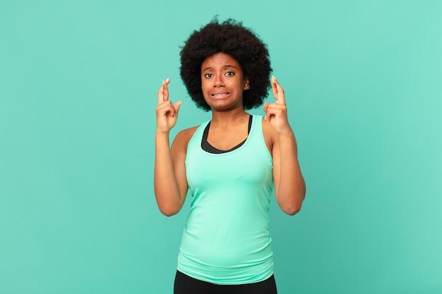 Zwarte afro-vrouw die angstig vingers kruist en hoopt op veel geluk met een bezorgde blik