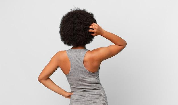 Zwarte afro-vrouw die denkt of twijfelt aan het krabben, zich verward en verward achter- of achteraanzicht voelt