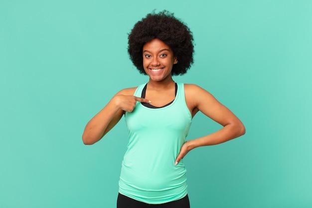 Zwarte afro-vrouw die er blij, trots en verrast uitziet, vrolijk naar zichzelf wijst, zelfverzekerd en verheven is