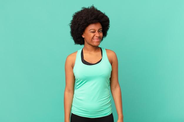 Zwarte afro-vrouw die er gelukkig en vriendelijk uitziet, lacht en je met een positieve houding aankijkt