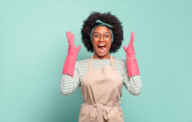 Zwarte afro-vrouw die met handen in de lucht schreeuwt, zich woedend, gefrustreerd, gestrest en boos voelt