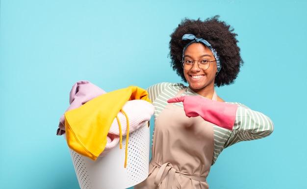 Zwarte afro-vrouw die vrolijk lacht, zich gelukkig voelt en naar de zijkant en naar boven wijst, object in kopie ruimte toont. huishoudelijk concept .. huishoudelijk concept