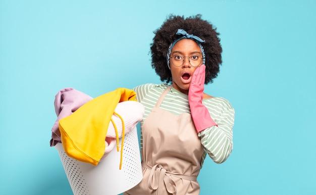 Zwarte afro vrouw die zich geschokt en bang voelt, doodsbang kijkt met open mond en handen op de wangen.