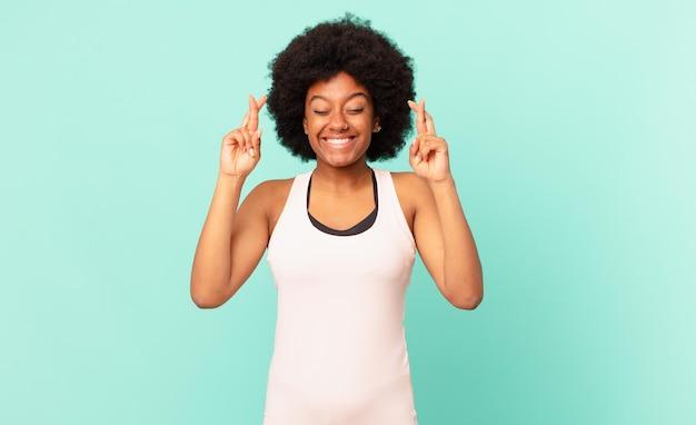 Zwarte afro-vrouw die zich nerveus en hoopvol voelt, vingers kruist, bidt en hoopt op geluk
