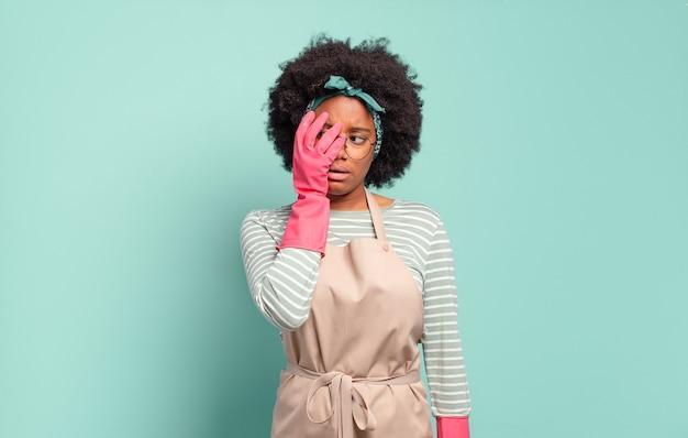 Zwarte afro vrouw die zich verveeld, gefrustreerd en slaperig voelt na een vermoeiende, saaie en vervelende taak, gezicht met hand vasthoudend. huishoudelijk concept