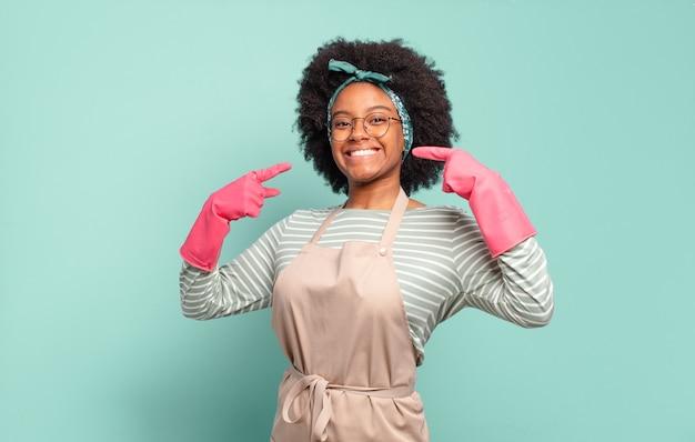 Zwarte afro vrouw glimlachend vol vertrouwen wijzend naar eigen brede glimlach, positieve, ontspannen, tevreden houding. huishoudelijk concept. huishoudelijk concept
