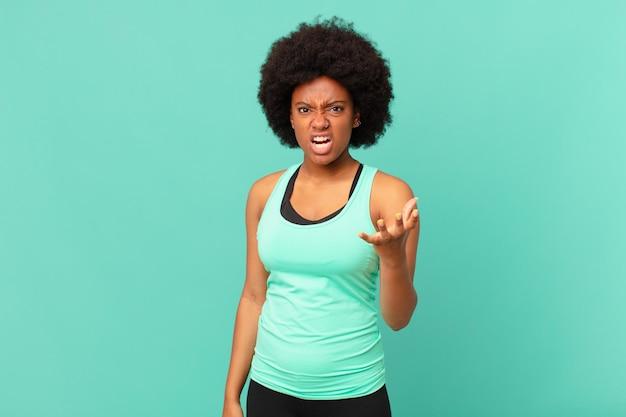 Zwarte afro-vrouw kijkt boos, geïrriteerd en gefrustreerd schreeuwend wtf of wat is er mis met jou