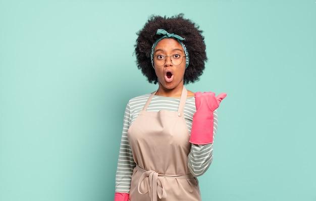 Zwarte afro-vrouw kijkt verbaasd in ongeloof, wijst naar een object aan de zijkant en zegt wow, ongelooflijk. huishoudconcept... huishoudconcept