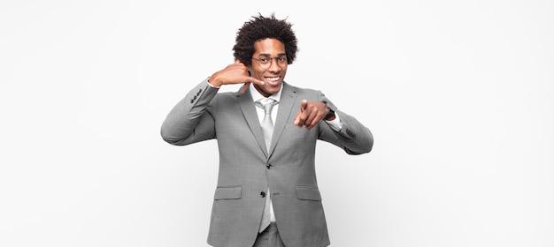 Zwarte afro-zakenlieden die vrolijk glimlachen en naar de camera wijzen terwijl ze je later bellen, telefoneren