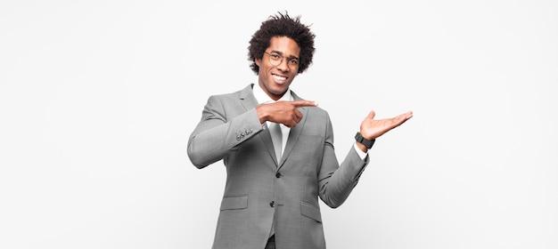 Zwarte afro zakenlieden vrolijk glimlachend en wijzend naar kopie ruimte op palm aan de zijkant, een object laten zien of adverteren