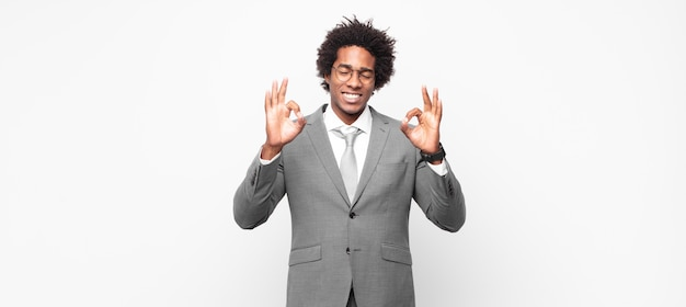 Zwarte afro zakenman die geconcentreerd kijkt en mediteert, zich tevreden en ontspannen voelt, nadenkt of een keuze maakt