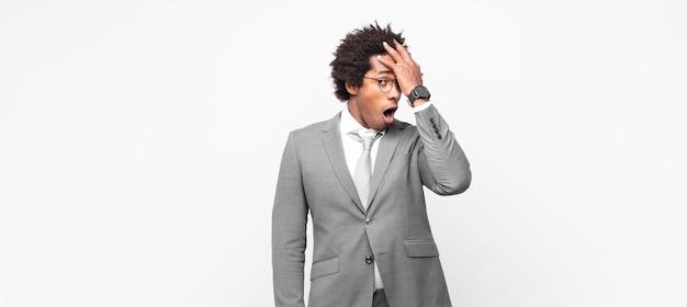 Zwarte afro-zakenman die handpalm naar voorhoofd opheft en denkt oeps, na een domme fout te hebben gemaakt of zich te herinneren, zich dom voelen Premium Foto
