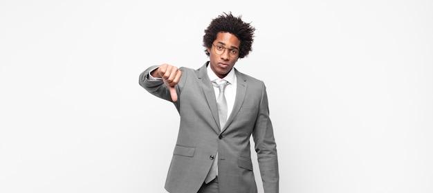 Zwarte afro zakenman die zich boos, boos, geïrriteerd, teleurgesteld of ontevreden voelt, duimen naar beneden toont met een serieuze blik