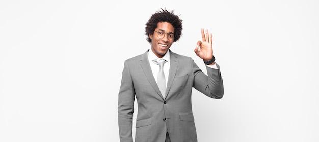 Zwarte afro zakenman die zich gelukkig, ontspannen en tevreden voelt, goedkeuring toont met een goed gebaar, glimlachend