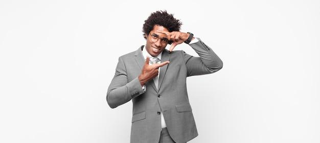Zwarte afro zakenman die zich gelukkig, vriendelijk en positief voelt, lacht en een portret of fotolijst met handen maakt