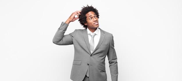 Zwarte afro zakenman die zich verbaasd en verward voelt, zijn hoofd krabt en naar de zijkant kijkt