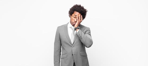 Zwarte afro zakenman die zich verveeld, gefrustreerd en slaperig voelt na een vermoeiende, saaie en vervelende taak, gezicht met de hand vasthoudt