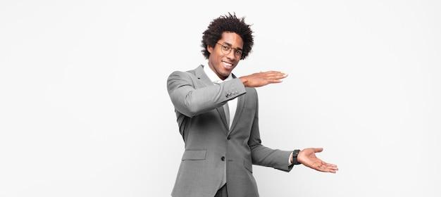 Zwarte afro-zakenman glimlacht, voelt zich gelukkig, positief en tevreden, houdt een object of concept vast of toont het op kopieerruimte