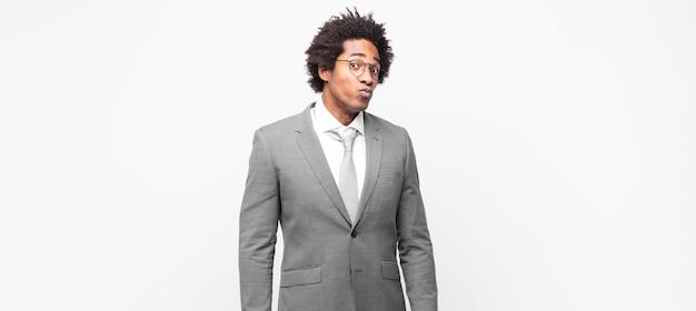Zwarte afro-zakenman met een gekke, gekke, verbaasde uitdrukking, puffende wangen, zich gevuld, dik en vol eten