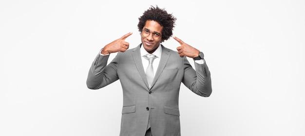 Zwarte afro-zakenman met een slechte houding die er trots en agressief uitziet, naar boven wijst of grappig teken met handen maakt