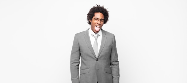 Zwarte afro zakenman met vrolijke, zorgeloze, rebelse houding, grappen maken en tong uitsteken, plezier maken