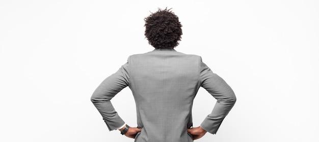 Zwarte afro zakenman, verward of vol of twijfels en vragen, zich afvragend, met de handen op de heupen, achteraanzicht
