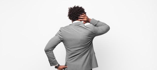 Zwarte afro zakenmantinkend of twijfelend, hoofd krabben, zich verbaasd en verward voelen, zicht naar achteren of naar achteren