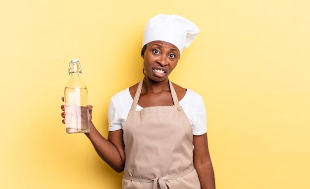Zwarte afrochef-vrouw die zich verbaasd en verward voelt, met een stomme, verbijsterde uitdrukking die naar iets onverwachts kijkt en een waterfles vasthoudt