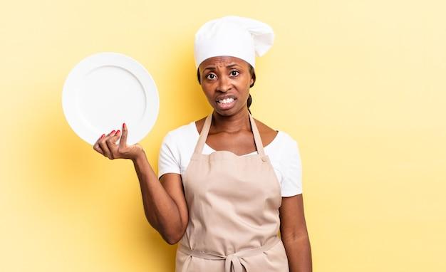 Zwarte afrochef-vrouw die zich verbaasd en verward voelt, met een stomme, verbijsterde uitdrukking die naar iets onverwachts kijkt. leeg bord concept