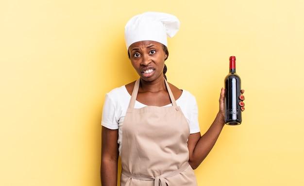 Zwarte afrochef-vrouw die zich verbaasd en verward voelt, met een stomme, verbijsterde uitdrukking die naar iets onverwachts kijkt. wijnfles concept