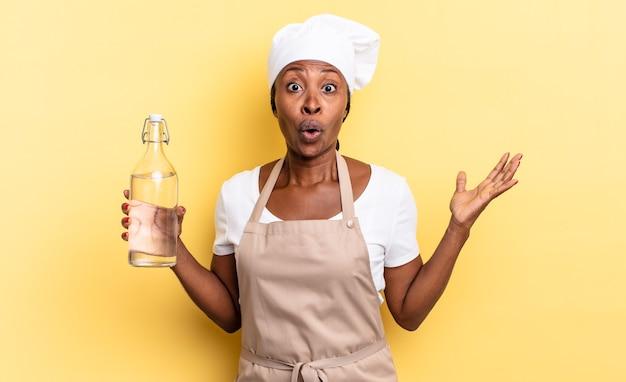 Zwarte afrochef-vrouw met open mond en verbaasd, geschokt en verbaasd met een ongelooflijke verrassing die een waterfles vasthoudt