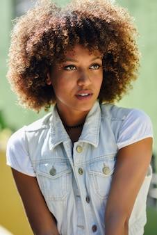 Zwarte, afrokapsel, die vrijetijdskleding op stedelijke achtergrond dragen