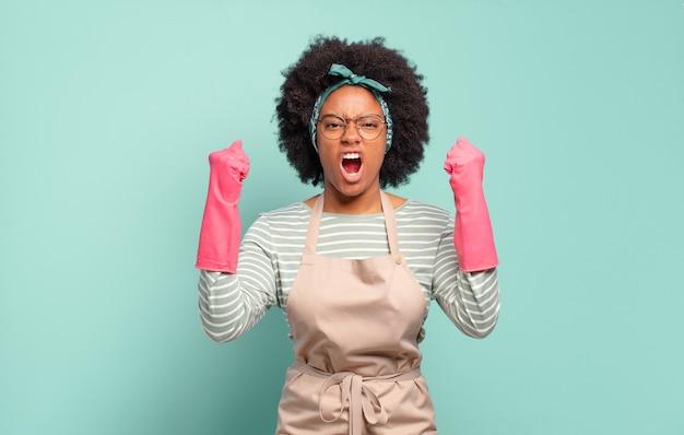 Zwarte afrovrouw die agressief schreeuwt. huishoudconcept... huishoudconcept