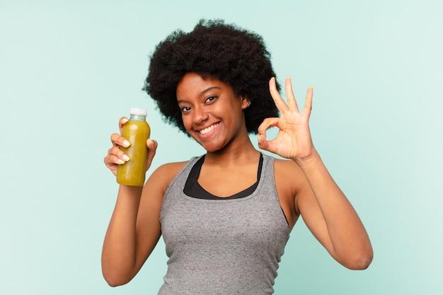 Zwarte afrovrouw die fitnesskleren draagt tegen geïsoleerde muur