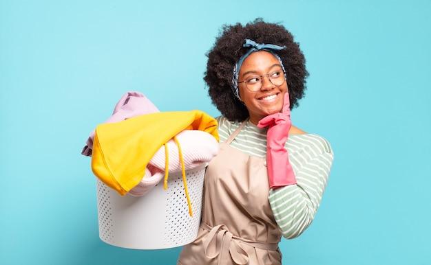 Zwarte afrovrouw die gelukkig glimlacht en dagdroomt of twijfelt, op zoek naar de kant. huishoudelijk concept .. huishoudelijk concept