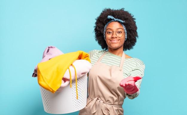 Zwarte afrovrouw die gelukkig glimlacht met vriendelijke, zelfverzekerde, positieve blik, die een voorwerp of concept aanbiedt en toont. huishoudelijk concept. huishoudelijk concept