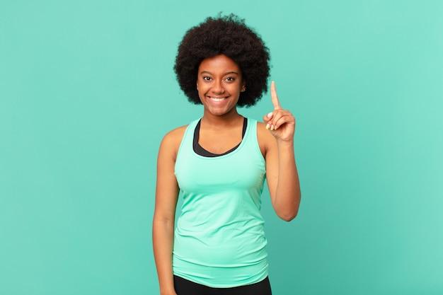 Zwarte afrovrouw die vrolijk en gelukkig met één hand naar boven glimlacht om ruimte te kopiëren