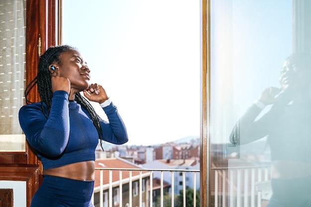 Zwarte afrovrouw gekleed in sportkleding die naar muziek luistert met een koptelefoon in een raam van haar huis omdat ze thuis gaat sporten vanwege de covid19 coronavirus pandemie