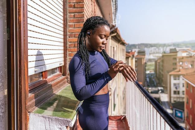 Zwarte afrovrouw in sportkleding die haar smartwatch aanraakt omdat ze thuis op het balkon gaat sporten vanwege de covid19 coronavirus pandemie