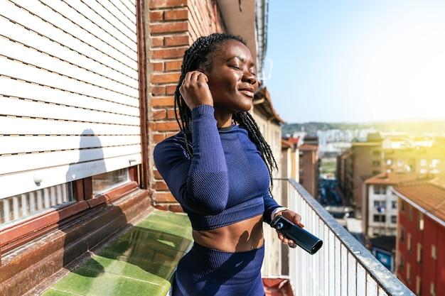 Zwarte afrovrouw in sportkleding die naar muziek luistert met een doos draadloze koptelefoons in haar hand op het balkon omdat ze thuis gaat sporten vanwege de covid19 coronavirus pandemie