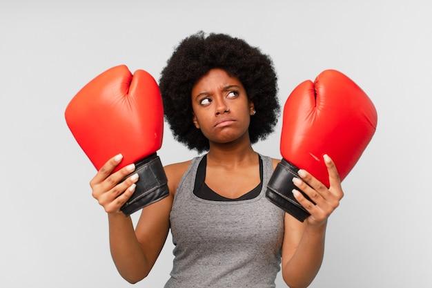 Zwarte afrovrouw met bokshandschoenen.
