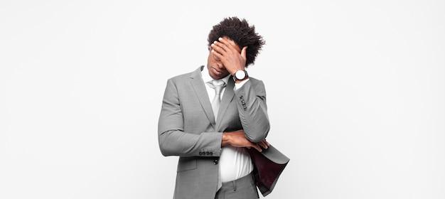 Zwarte afrozakenman die beklemtoond, beschaamd of overstuur kijkt, met hoofdpijn, gezicht bedekt met hand