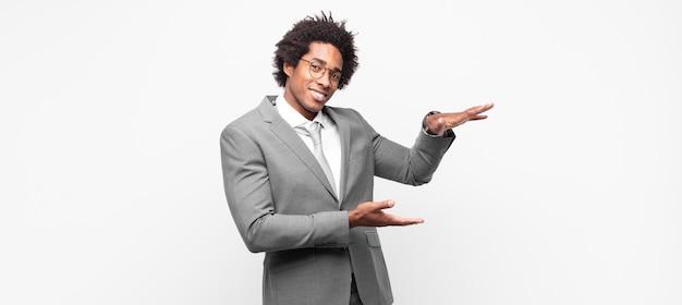 Zwarte afrozakenman die een voorwerp met beide handen op de zijexemplaarruimte houdt, een voorwerp toont, aanbiedt of adverteert