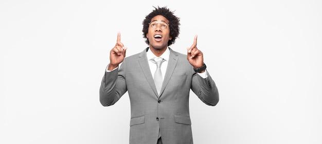 Zwarte afrozakenman die geschokt, verbaasd en met open mond kijkt, naar boven wijzend met beide handen om ruimte te kopiëren